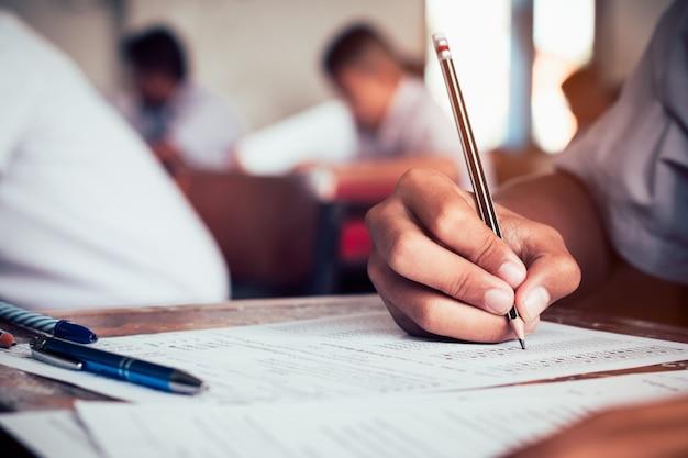 Primo piano alla matita della tenuta dello studente e scrittura dell'esame finale nella stanza dell'esame o studio in aula. stile dell'annata