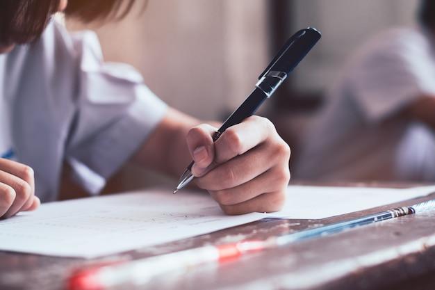 Primo piano alla penna di tenuta dello studente e alla scrittura dell'esame finale