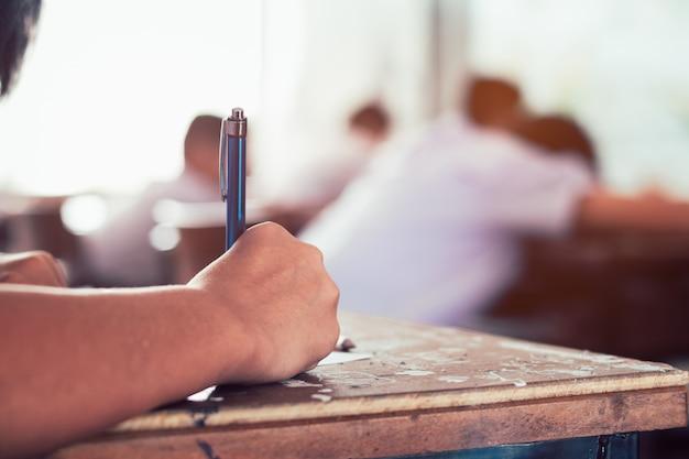Primo piano alla penna di tenuta dello studente e scrittura dell'esame finale nella stanza dell'esame o studio in aula.