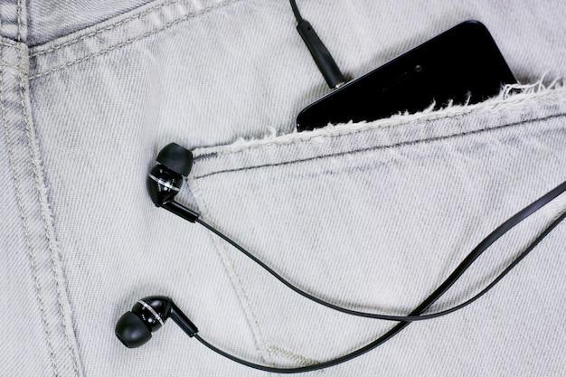 Primo piano alla tasca dei jeans con smartphone e cuffie