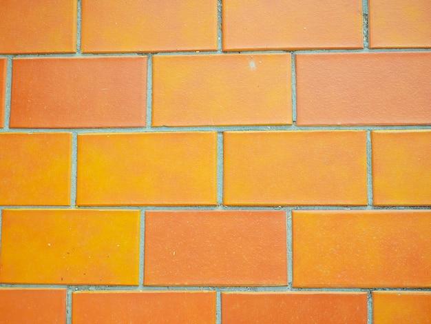 Primo piano arancione delle mattonelle della parete. trama di sfondo. orange brick wal