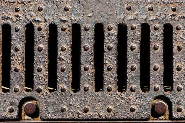 Primo piano arrugginito della griglia della fogna del metallo