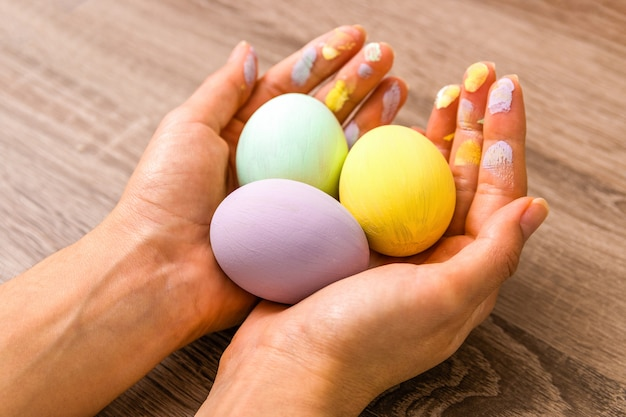Primo piano bella donna mani in possesso di tre uova colorate in teneri colori pastello giallo, menta e viola sul tavolo di legno