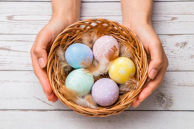 Primo piano bella donna mani in possesso di un cesto di vimini con uova di pasqua dipinte a mano in teneri colori pastello e piuma sul tavolo di legno