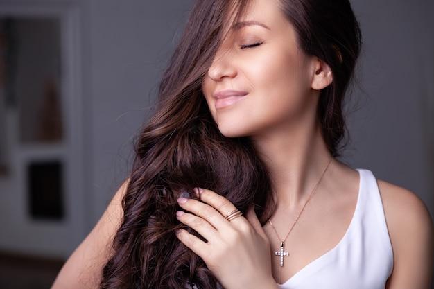 Primo piano bella ragazza bruna con i capelli lunghi in orecchini gioielli in argento, anelli, bracciale, catena, collana.
