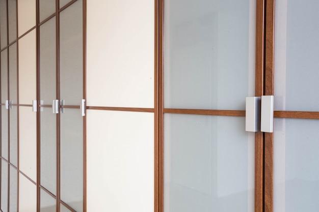Primo piano bianco di legno delle porte dell'armadio per nuova progettazione moderna dei vestiti
