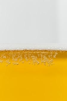 Primo piano bicchiere di birra con schiuma