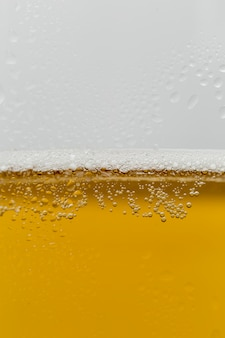 Primo piano bicchiere di birra rinfrescante con schiuma