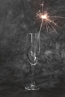 Primo piano bicchiere di champagne con stecca scintillante