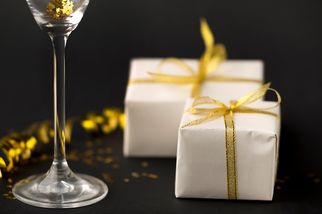 Primo piano bicchiere di champagne e regali