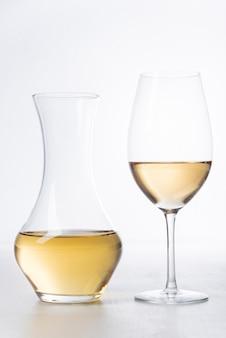 Primo piano bicchiere di vino bianco e decanter