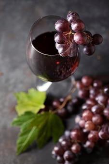 Primo piano bicchiere di vino circondato da uva
