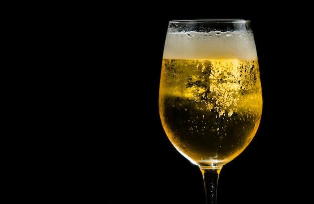 Primo piano birra d'oro nel bicchiere contro il buio.