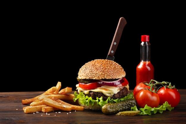 Primo piano casalingo dell'hamburger con la bottiglia del manzo, del pomodoro, della lattuga, del formaggio e della salsa sulla tavola di legno. nell'hamburger infilò un coltello. fastfood su sfondo scuro