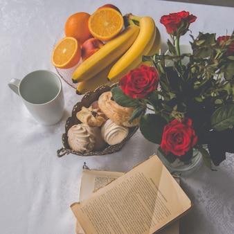 Primo piano che serve piatti sul tavolo: tazze, frutta, banane, arance, biscotti, fiori in un vaso. vedi sopra
