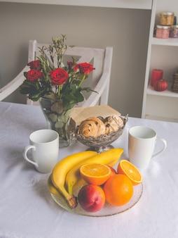 Primo piano che serve piatti sul tavolo: tazze, frutta, banane, arance, biscotti, fiori in un vaso.
