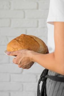 Primo piano che tiene pane rotondo fresco