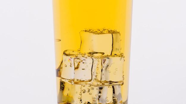Primo piano con bicchiere di bevanda e cubetti di ghiaccio