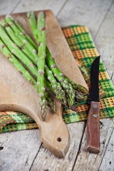 Primo piano crudo del coltello e dell'asparago sul tagliere sulla tavola di legno rustica