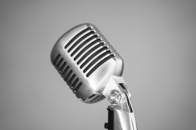 Primo piano d'argento d'annata del microfono su fondo grigio. concetto di musica retrò oldies.