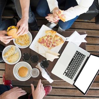 Primo piano degli amici che mangiano spuntino con le bevande e computer portatile sul tavolo