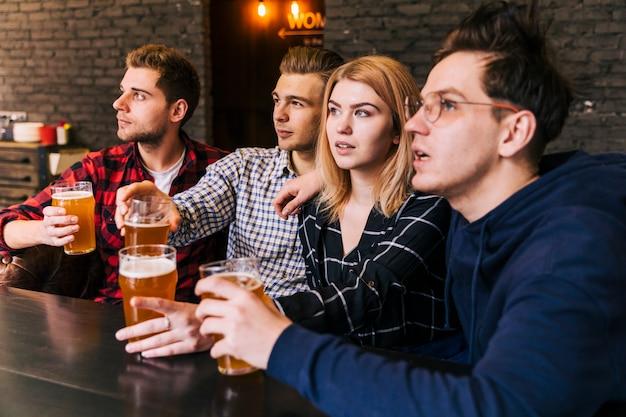Primo piano degli amici che tengono i vetri di birra che osservano via