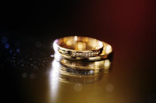 Primo piano degli anelli dorati di cerimonia nuziale su oscurità
