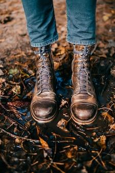 Primo piano degli stivali graffiati d'annata delle gambe del `s dell'uomo che stanno nella pozza.