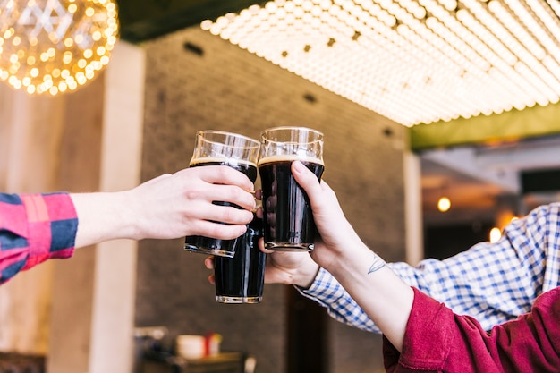 Primo piano degli uomini che tintinnano i vetri di birra in pub