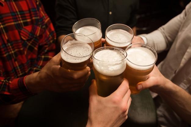 Primo piano degli uomini che tostano con la birra