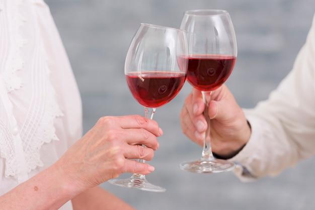 Primo piano dei bicchieri di vino tintinnanti di una coppia contro fondo vago