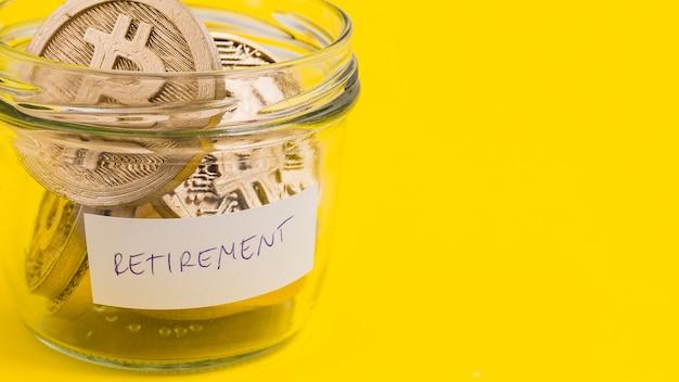 Primo piano dei bitcoins nel barattolo di vetro di pensionamento su fondo giallo