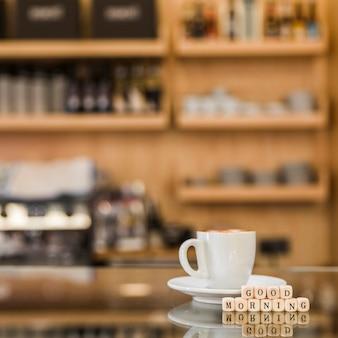 Primo piano dei blocchetti di legno di buongiorno con la tazza di caffè sul gabinetto di vetro