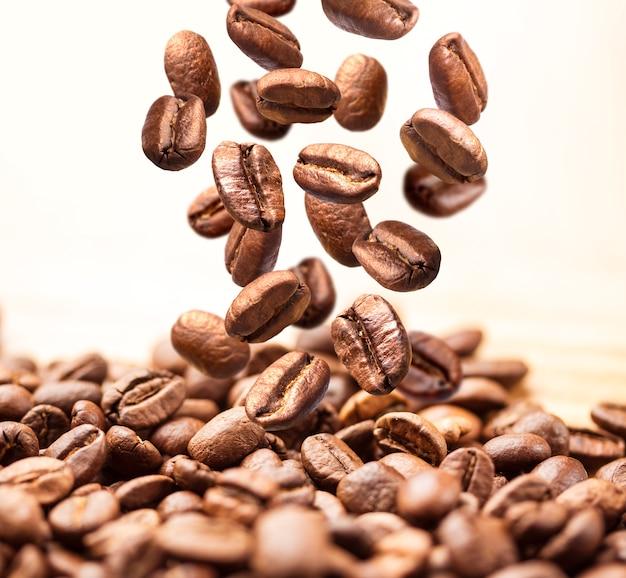 Primo piano dei chicchi di caffè di caduta o di volo su bianco