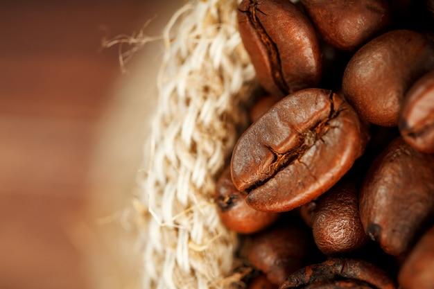 Primo piano dei chicchi di caffè nella borsa di tela da imballaggio su superficie di legno