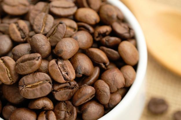 Primo piano dei chicchi di caffè nella tazza bianca.