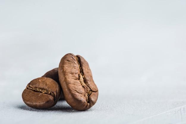 Primo piano dei chicchi di caffè su fondo bianco con copyspace