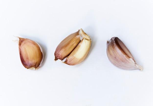 Primo piano dei chiodi di garofano di aglio su fondo bianco
