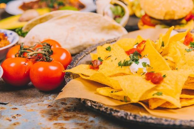 Primo piano dei chip messicani gialli del nacho con il pomodoro ciliegia