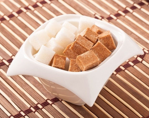 Primo piano dei cubi di zucchero bianco e marrone