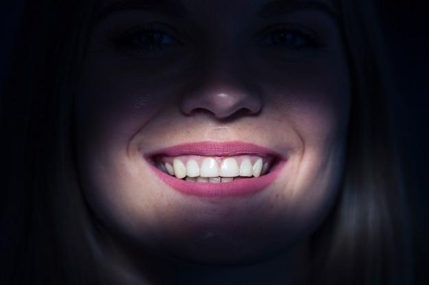 Primo piano dei denti illuminati di una donna