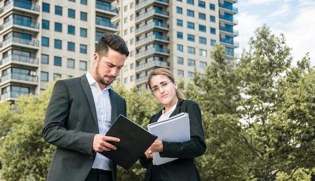 Primo piano dei documenti della tenuta della donna di affari e dell'uomo d'affari che stanno davanti a costruzione