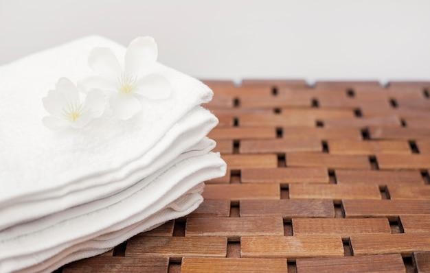 Primo piano dei fiori bianchi e dell'asciugamano sul ripiano del tavolo di legno