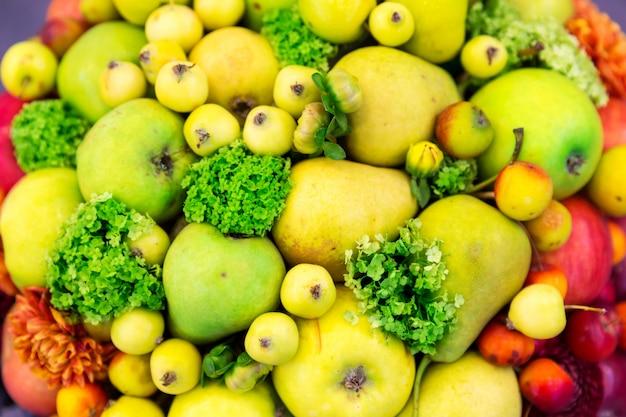 Primo piano dei fiori e dei frutti, raccolto fresco. cibo vitaminico e decorazioni floreali