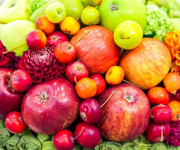 Primo piano dei fiori e delle mele, raccolto fresco. cibo vitaminico e decorazioni floreali