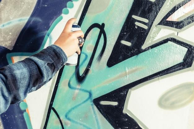 Primo piano dei graffiti della pittura della mano di un artista sulla parete