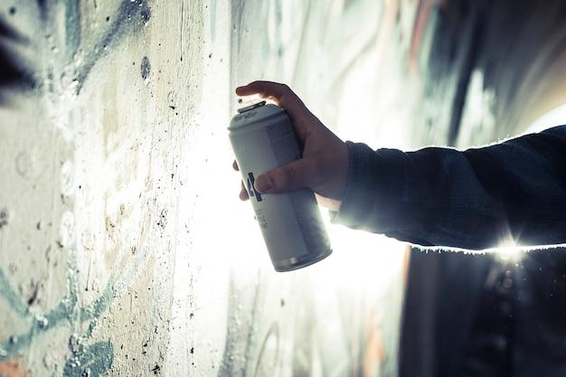 Primo piano dei graffiti della pittura della mano di una persona con la latta di spruzzo sulla parete