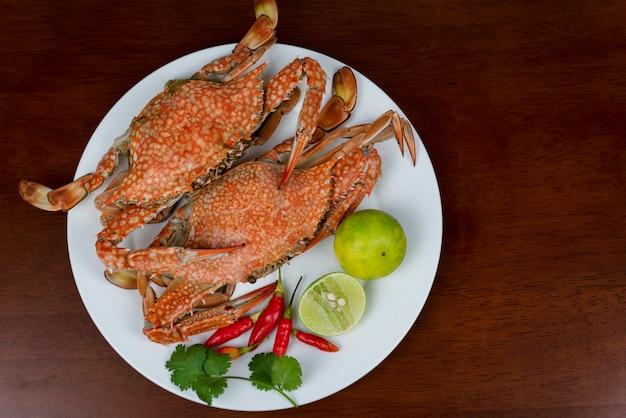 Primo piano dei granchi blu con la salsa di immersione dei frutti di mare tailandesi su un piatto, su un fondo di legno, vista superiore