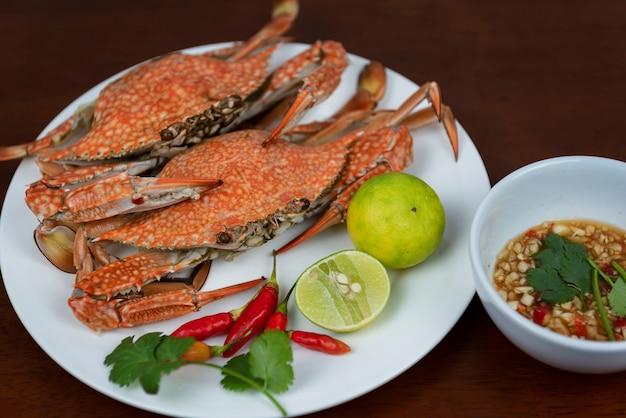 Primo piano dei granchi blu con la salsa di immersione dei frutti di mare tailandesi su un piatto