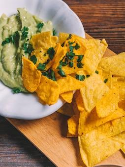 Primo piano dei nachos e del guacamole messicani in ciotola sul tagliere di legno